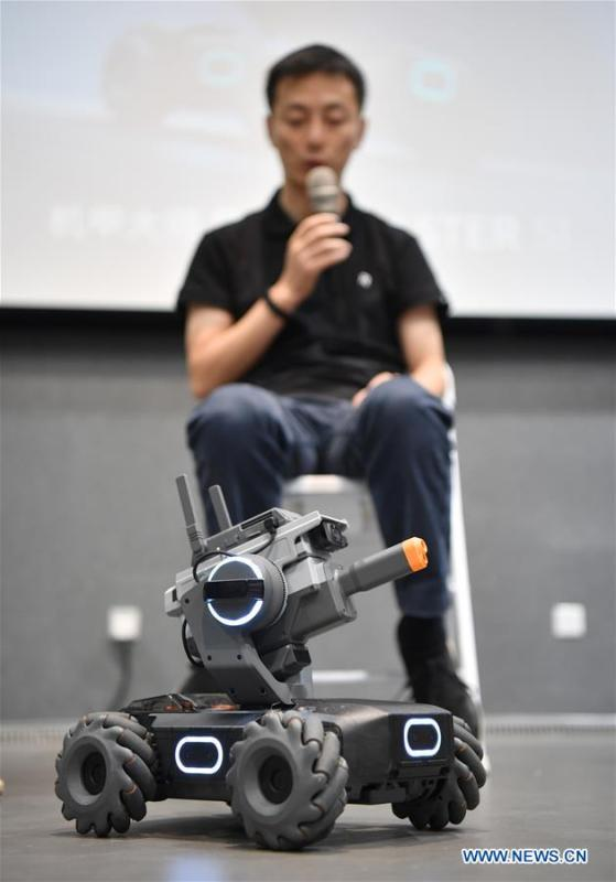 A staff member explains as an educational robot produced by Chinese drone maker DJI reacts at an event in Beijing, capital of China, June 12, 2019. DJI launched its first educational robot RoboMaster S1 at an event on Wednesday. The robot, supporting 2 programming languages, features a configuration of 31 sensors and 46 programmable components. (Xinhua/Wang Qingqin)