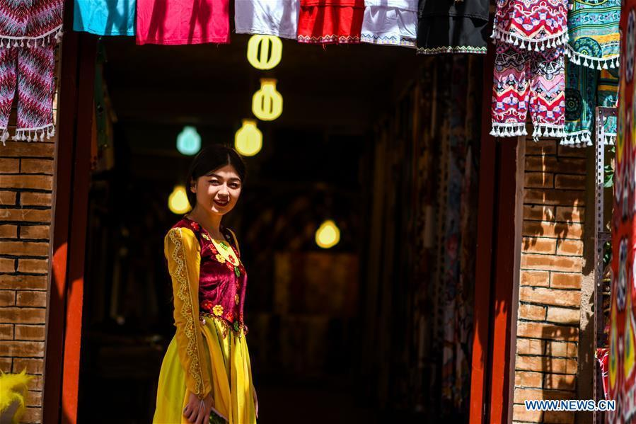 A staff member poses for a photo outside a shop in the ancient city of Kashgar, northwest China\'s Xinjiang Uygur Autonomous Region, June 12, 2019. The ancient city of Kashgar has been well prepared for the peak tourism season through multiple measures including improving infrastructure and service quality as well as staging acrobatics performances to help tourists better experience the time-honored folk culture here. (Xinhua/Zhao Ge)