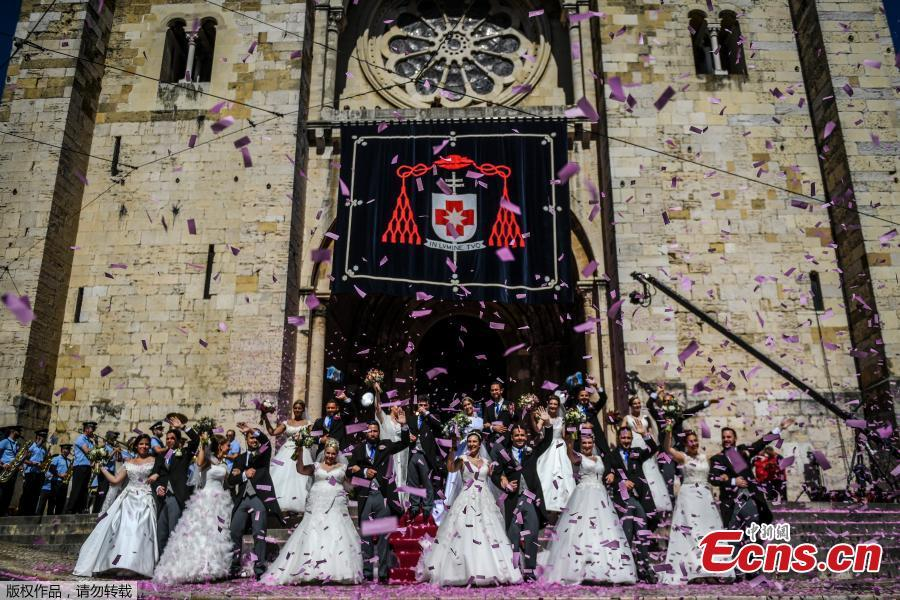 Brides and grooms pose for a photo outside the Lisbon\'s cathedral following their wedding ceremony in Lisbon on June 12, 2019. It is Lisbon\'s wedding of the year. Crowds gather at the cathedral, hoping to catch a glimpse of the newlyweds as cameras lie in wait. Then not one, but 11 couples walk out, fresh from tying the knot today in an all-expenses-paid ceremony, the beneficiaries of a decades-long annual tradition that fetes the Portuguese capital\'s beloved patron Saint Anthony, matchmaker extraordinaire.(Photo/Agencies)