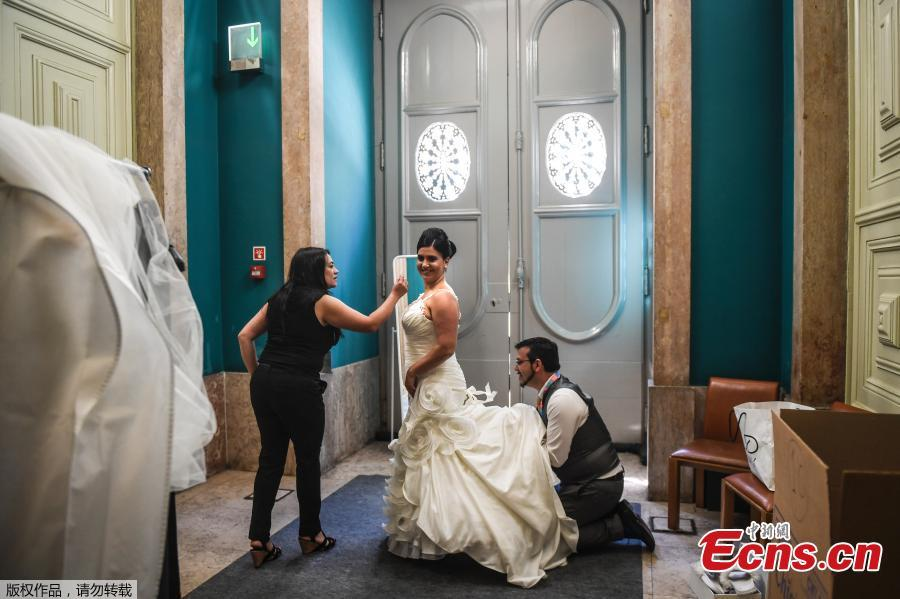 A bridal gown designer helps a bride to get dressed before celebrating a multiple civil ceremony at the Lisbon\'s city hall, during Saint Anthony\'s day on June 12, 2019. It is Lisbon\'s wedding of the year. Crowds gather at the cathedral, hoping to catch a glimpse of the newlyweds as cameras lie in wait. Then not one, but 11 couples walk out, fresh from tying the knot today in an all-expenses-paid ceremony, the beneficiaries of a decades-long annual tradition that fetes the Portuguese capital\'s beloved patron Saint Anthony, matchmaker extraordinaire. (Photo/Agencies)
