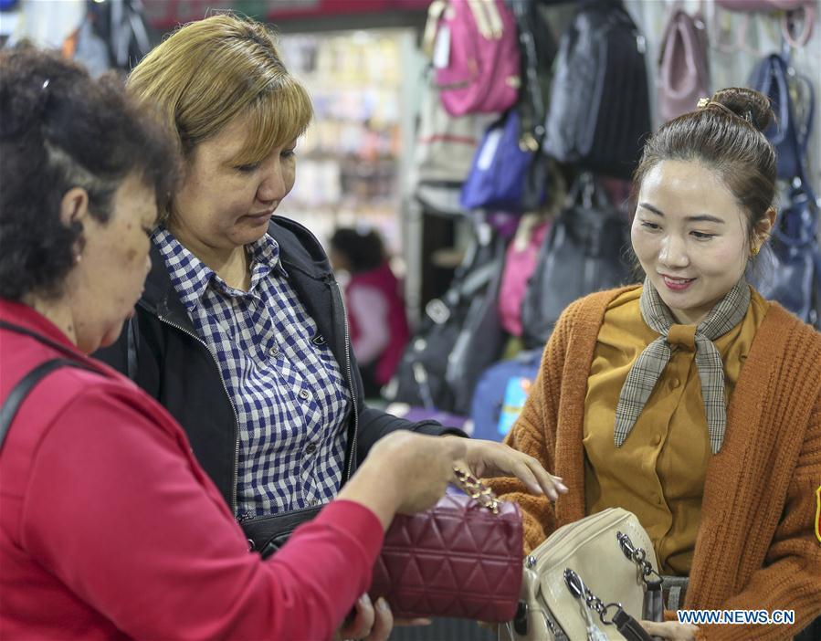 A trader (C) from Kazakhstan learns about the wholesale price of bags and suitcases at a shopping mall in the China-Kazakhstan Horgos International Border Cooperation Center in Horgos, northwest China\'s Xinjiang Uygur Autonomous Region, June 12, 2019. With the Belt and Road Initiative, the trade between Xinjiang, Kyrgyzstan and Tajikistan has continued to develop. On the southern border of Xinjiang, three ports, Turugart, Erkeshtam and Karasu, between China and Kyrgyzstan and Tajikistan, saw large quantities of goods cleared by customs every year. (Xinhua/Zhou Xu)
