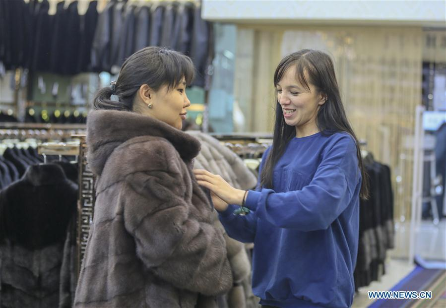 A trader from Kazakhstan helps a customer try on clothes at the China-Kazakhstan Horgos International Border Cooperation Center in Horgos, northwest China\'s Xinjiang Uygur Autonomous Region, June 12, 2019. With the Belt and Road Initiative, the trade between Xinjiang, Kyrgyzstan and Tajikistan has continued to develop. On the southern border of Xinjiang, three ports, Turugart, Erkeshtam and Karasu, between China and Kyrgyzstan and Tajikistan, saw large quantities of goods cleared by customs every year. (Xinhua/Zhou Xu)