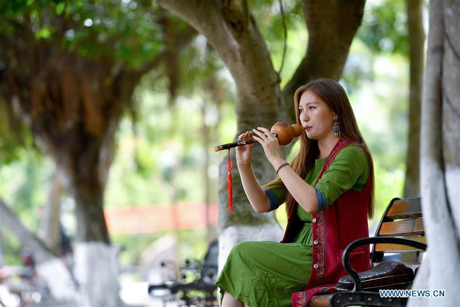Takyrbasheva Asel, a student from Kyrgyzstan, plays the Hulusi, a free-reed wind instrument from China, at the campus of Hainan University in Haikou, south China\'s Hainan Province, June 13, 2019. Kyrgyz girl Takyrbasheva Asel majors in Tourism Management in Hainan University. She has dedicated herself in experiencing the Chinese culture, including the learning of traditional Chinese musical instruments, Taiji and martial arts, and tea art since she came to China three years ago. She hoped she could stay in China after graducation and invite people from her hometown to come and experience the Chinese culture. Statistics showed that over 4,600 Kyrgyz students studied in China in 2018. (Xinhua/Guo Cheng)