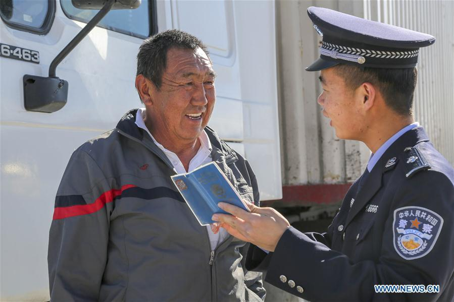 A Chinese border policeman introduces entry-exit related matters to a driver from Kyrgyzstan in Erkeshtam port, northwest China\'s Xinjiang Uygur Autonomous Region, June 11, 2019. With the Belt and Road Initiative, the trade between Xinjiang, Kyrgyzstan and Tajikistan has continued to develop. On the southern border of Xinjiang, three ports, Turugart, Erkeshtam and Karasu, between China and Kyrgyzstan and Tajikistan, saw large quantities of goods cleared by customs every year. (Xinhua/Luo Yang)