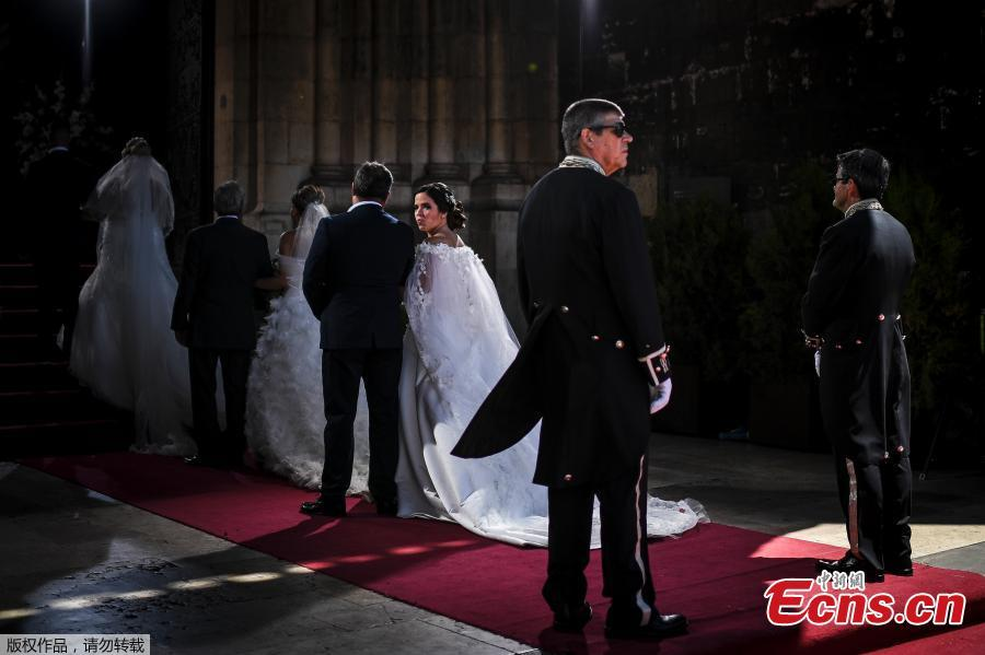 Brides and their best-men queue to enter the cathedral ahead of the celebration of a multiple wedding ceremony in Lisbon on June 12, 2019. It is Lisbon\'s wedding of the year. Crowds gather at the cathedral, hoping to catch a glimpse of the newlyweds as cameras lie in wait. Then not one, but 11 couples walk out, fresh from tying the knot today in an all-expenses-paid ceremony, the beneficiaries of a decades-long annual tradition that fetes the Portuguese capital\'s beloved patron Saint Anthony, matchmaker extraordinaire.(Photo/Agencies)