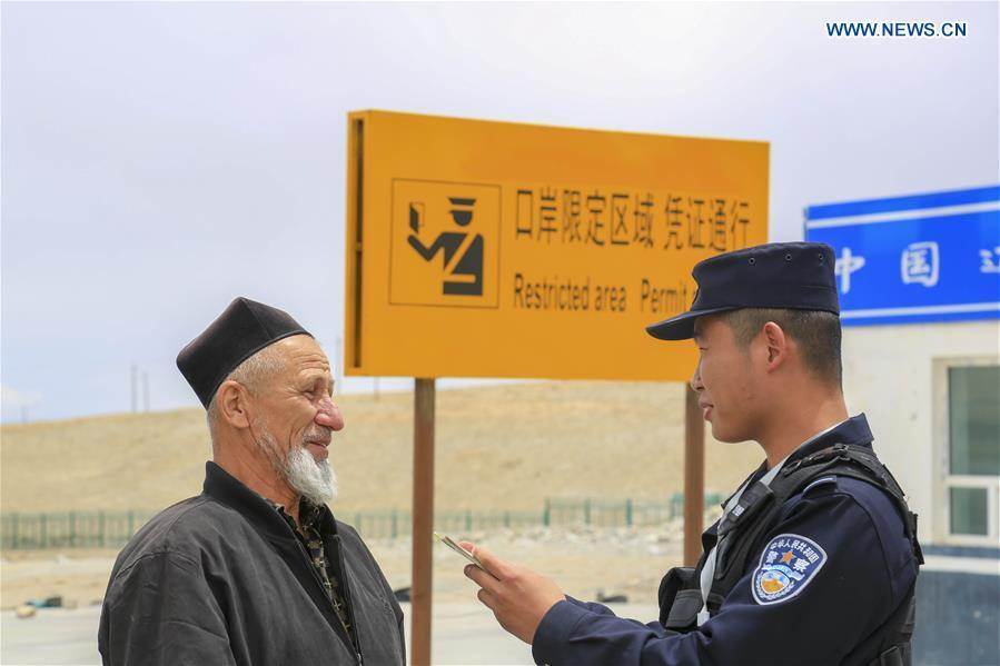 A Chinese border policeman checks information of a man from Tajikistan at the Karasu port in Tajik Autonomous County of Taxkorgan, northwest China\'s Xinjiang Uygur Autonomous Region, on June 11, 2019. With the Belt and Road Initiative, trade between China and Tajikistan has continued to develop. The Karasu port between the two countries has seen large quantities of goods cleared by customs every year. (Xinhua/Huang Huan)