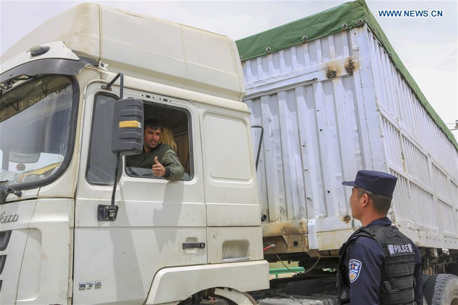 A driver from Tajikistan gestures to a Chinese border policeman at the Karasu port in Tajik Autonomous County of Taxkorgan, northwest China\'s Xinjiang Uygur Autonomous Region, on June 11, 2019. With the Belt and Road Initiative, trade between China and Tajikistan has continued to develop. The Karasu port between the two countries has seen large quantities of goods cleared by customs every year. (Xinhua/Huang Huan)