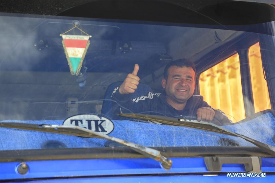 A driver from Tajikistan thumbs up to greet in Karasu port, northwest China\'s Xinjiang Uygur Autonomous Region, June 11, 2019. With the Belt and Road Initiative, the trade between Xinjiang, Kyrgyzstan and Tajikistan has continued to develop. On the southern border of Xinjiang, three ports, Turugart, Erkeshtam and Karasu, between China and Kyrgyzstan and Tajikistan, saw large quantities of goods cleared by customs every year. (Xinhua/Huang Huan)