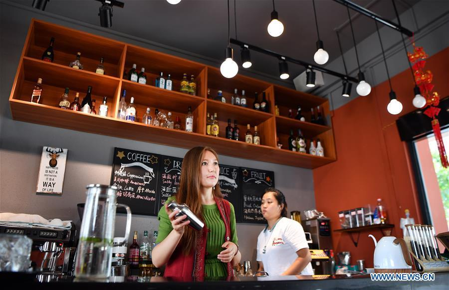 Takyrbasheva Asel (L), a student from Kyrgyzstan, works at a coffee shop during her spare time in Hainan University in Haikou, south China\'s Hainan Province, June 13, 2019. Kyrgyz girl Takyrbasheva Asel majors in Tourism Management in Hainan University. She has dedicated herself in experiencing the Chinese culture, including the learning of traditional Chinese musical instruments, Taiji and martial arts, and tea art since she came to China three years ago. She hoped she could stay in China after graducation and invite people from her hometown to come and experience the Chinese culture. Statistics showed that over 4,600 Kyrgyz students studied in China in 2018. (Xinhua/Guo Cheng)