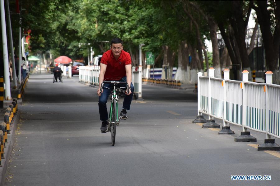 Sadyrbek, a Kyrgyz PhD candidate studying in China, goes by bike to the office of Xinjiang Institute of Ecology and Geography of Chinese Academy of Sciences in Urumqi, northwest China\'s Xinjiang Uygur Autonomous Region, June 11, 2019. (Xinhua/Bai Jiali)