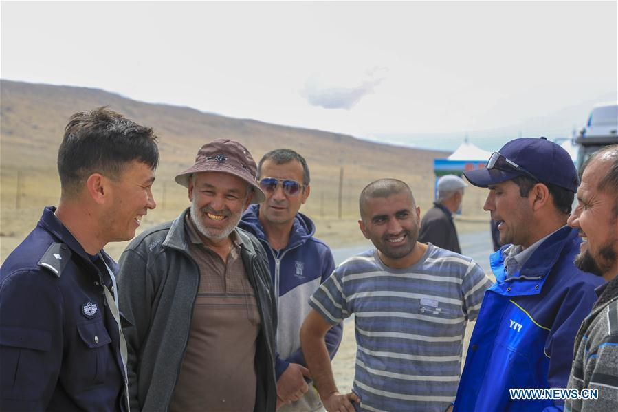 A Chinese border policeman (1st L) introduces entry-exit related matters to drivers from Tajikistan in Karasu port, northwest China\'s Xinjiang Uygur Autonomous Region, June 11, 2019. With the Belt and Road Initiative, the trade between Xinjiang, Kyrgyzstan and Tajikistan has continued to develop. On the southern border of Xinjiang, three ports, Turugart, Erkeshtam and Karasu, between China and Kyrgyzstan and Tajikistan, saw large quantities of goods cleared by customs every year. (Xinhua/Huang Huan)