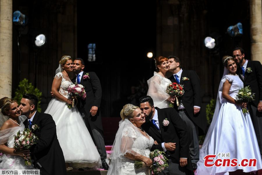 Brides and grooms kiss as they pose for a photo outside the Lisbon\'s Cathedral following their wedding ceremony in Lisbon on June 12, 2019. It is Lisbon\'s wedding of the year. Crowds gather at the cathedral, hoping to catch a glimpse of the newlyweds as cameras lie in wait. Then not one, but 11 couples walk out, fresh from tying the knot today in an all-expenses-paid ceremony, the beneficiaries of a decades-long annual tradition that fetes the Portuguese capital\'s beloved patron Saint Anthony, matchmaker extraordinaire.(Photo/Agencies)