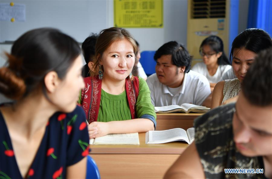Takyrbasheva Asel, a student from Kyrgyzstan, talks with classmates in Hainan University in Haikou, south China\'s Hainan Province, June 13, 2019. Kyrgyz girl Takyrbasheva Asel majors in Tourism Management in Hainan University. She has dedicated herself in experiencing the Chinese culture, including the learning of traditional Chinese musical instruments, Taiji and martial arts, and tea art since she came to China three years ago. She hoped she could stay in China after graducation and invite people from her hometown to come and experience the Chinese culture. Statistics showed that over 4,600 Kyrgyz students studied in China in 2018. (Xinhua/Guo Cheng)