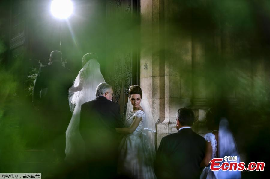 Brides and their best-men queue to enter the cathedral ahead of the celebration of a multiple wedding ceremony in Lisbon on June 12, 2019. It is Lisbon\'s wedding of the year. Crowds gather at the cathedral, hoping to catch a glimpse of the newlyweds as cameras lie in wait. Then not one, but 11 couples walk out, fresh from tying the knot today in an all-expenses-paid ceremony, the beneficiaries of a decades-long annual tradition that fetes the Portuguese capital\'s beloved patron Saint Anthony, matchmaker extraordinaire. (Photo/Agencies)