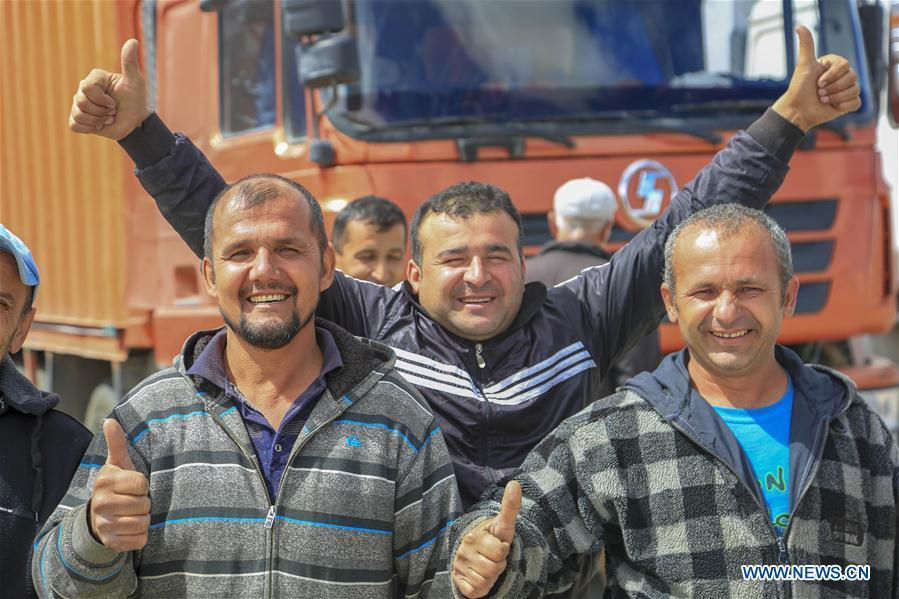 Passengers from Tajikistan pose for a group photo in Karasu port, northwest China\'s Xinjiang Uygur Autonomous Region, June 11, 2019. With the Belt and Road Initiative, the trade between Xinjiang, Kyrgyzstan and Tajikistan has continued to develop. On the southern border of Xinjiang, three ports, Turugart, Erkeshtam and Karasu, between China and Kyrgyzstan and Tajikistan, saw large quantities of goods cleared by customs every year. (Xinhua/Huang Huan)