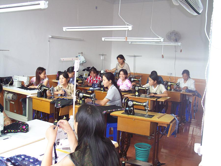 Seamstresses work at the Shenani workshop in 2004.  (Photo provided to chinadaily.com.cn)