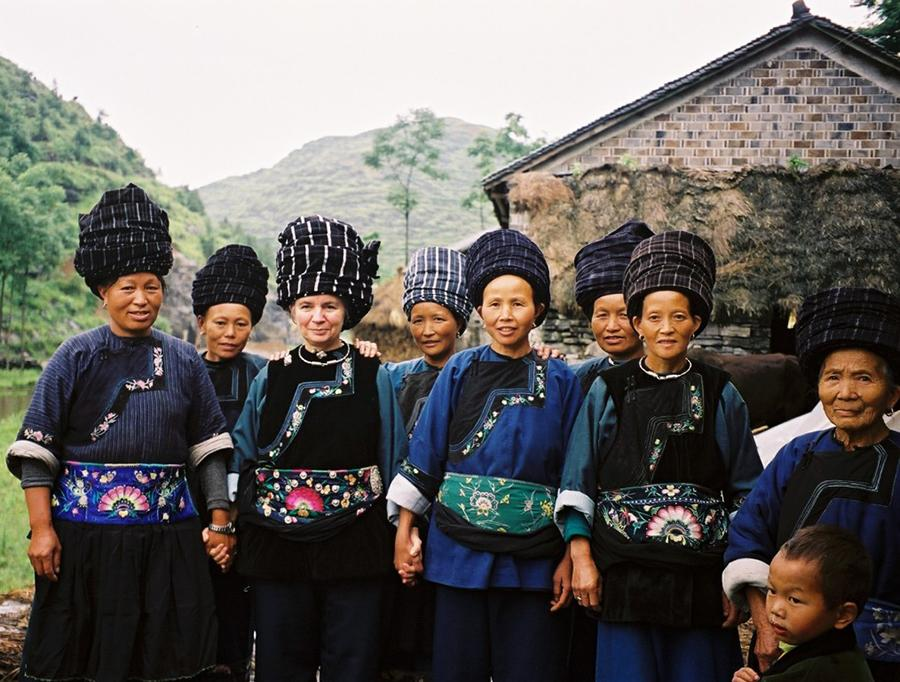 Dorothy Lacy, third from left, and some of the craftswomen who create embroidered items for the Shenaini website pose in Miao traditional costume in 2006. (Photo provided to chinadaily.com.cn)
