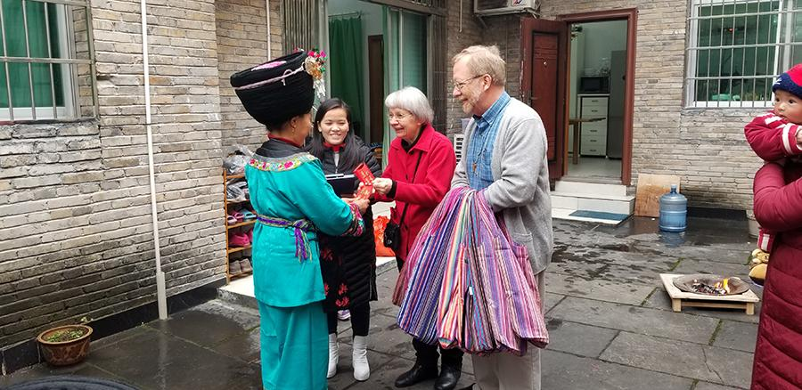 Paul and Dorothy Lacy give a gift in a red envelope to a Miao woman who is one of their \