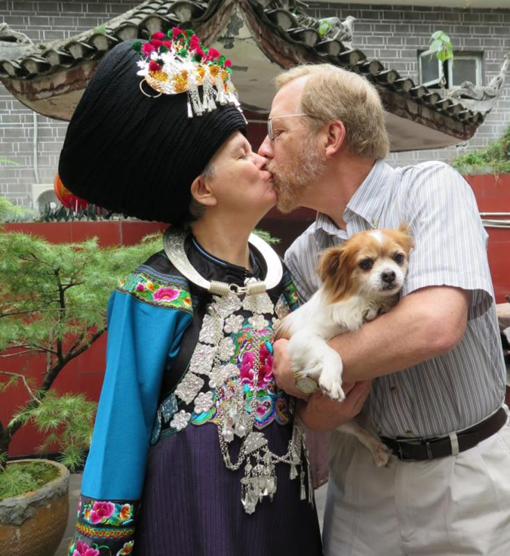 Paul Lacy and his wife, Dorothy, who is dressed in traditional Miao costume, share a kiss. (Photo provided to chinadaily.com.cn)