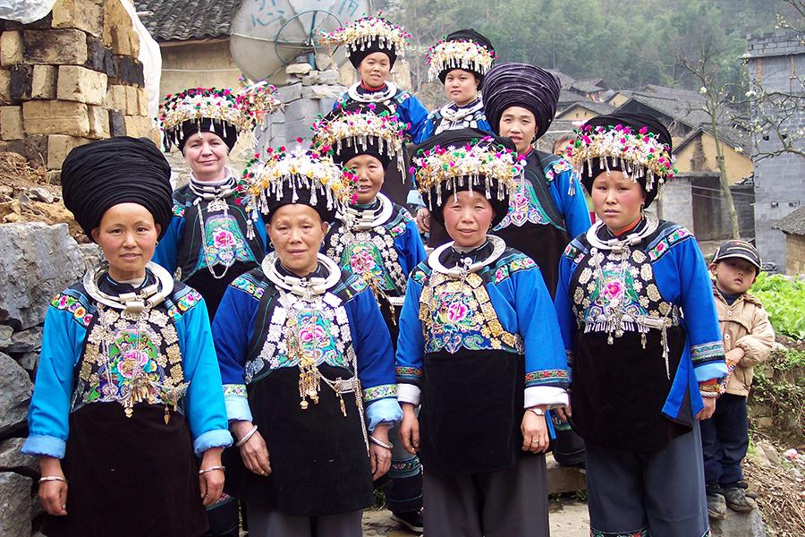 Dorothy Lacy, second row, left, and some of the craftswomen who create embroidered items for the Shenaini website pose in Miao traditional costume in 2006. (Photo provided to chinadaily.com.cn)
