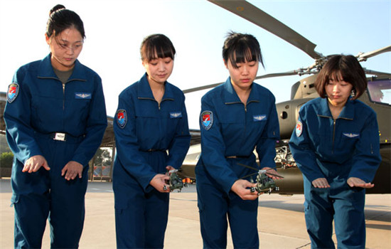 Four of the People's Liberation Army's first five female combat helicopter pilots review maneuvers during training in October 2014.(Chen Kai/ For China Daily)