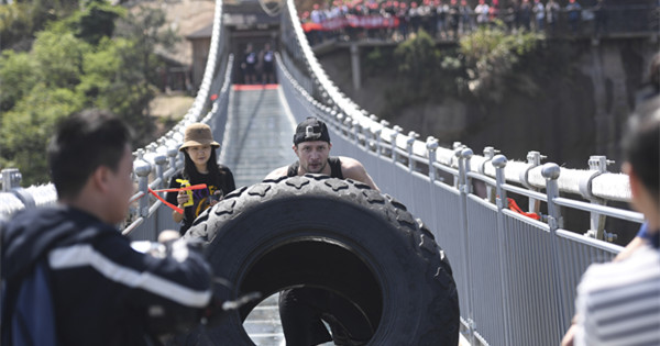 Tire flip challenges strongmen on suspended glass bridge