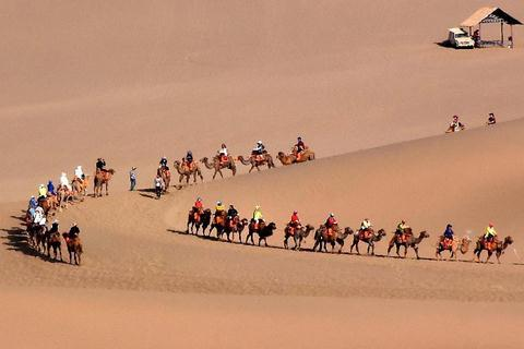 Tourists enjoy themselves at Mingsha Hill desert
