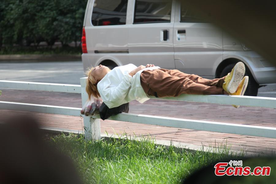 Woman sleeps on 5-cm-wide roadside railing in Harbin