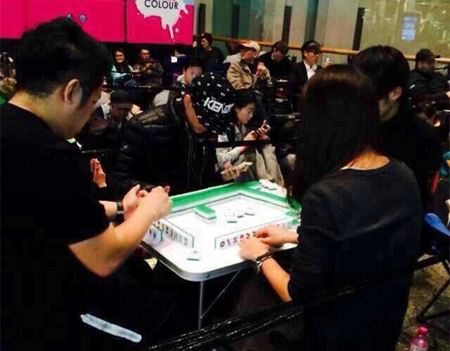 Fans play mahjong to kill time waiting in line for iPhone 6