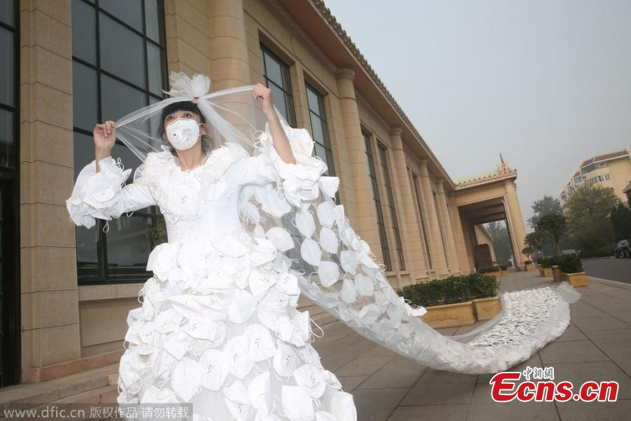 Girl in wedding dress made with masks stages anti-smog themed show