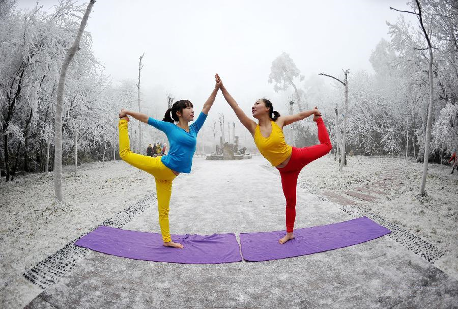 Women do yoga in Hunan's Tianmenshan after snowfall