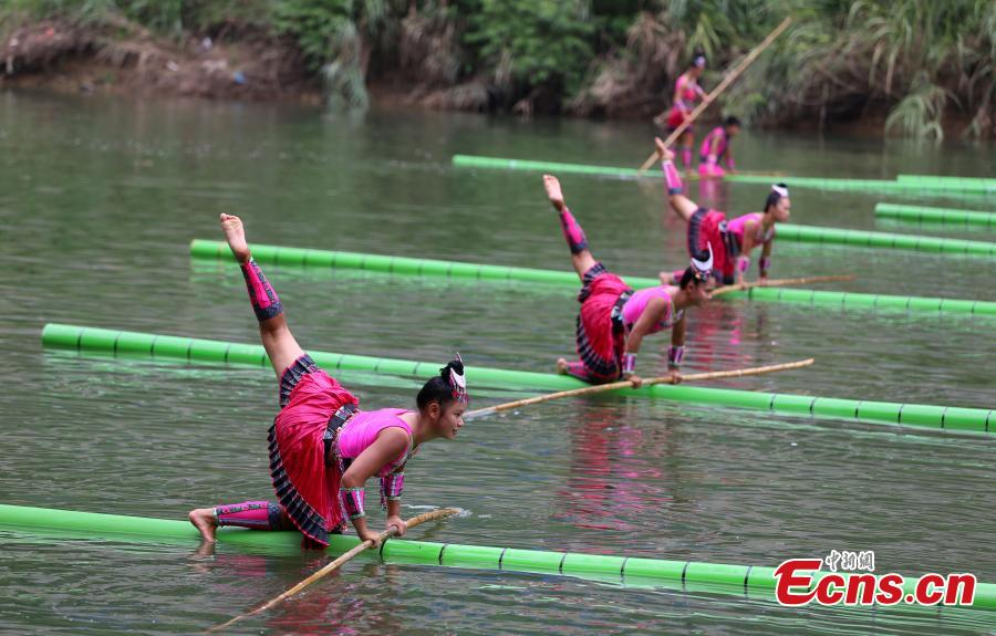 Students practice traditional water dance on bamboo trunks