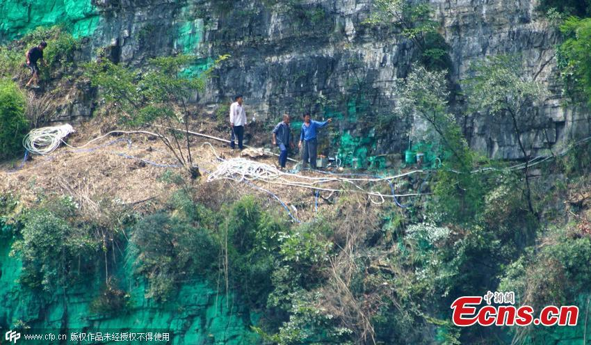 Villager paints cliff wall green for good luck