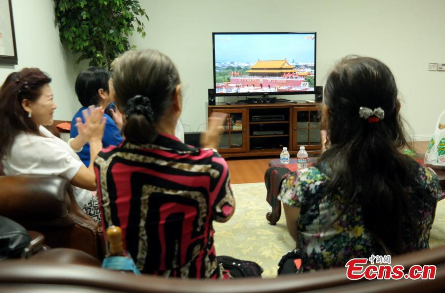 Overseas Chinese watch V-Day parade on TV in Los Angeles