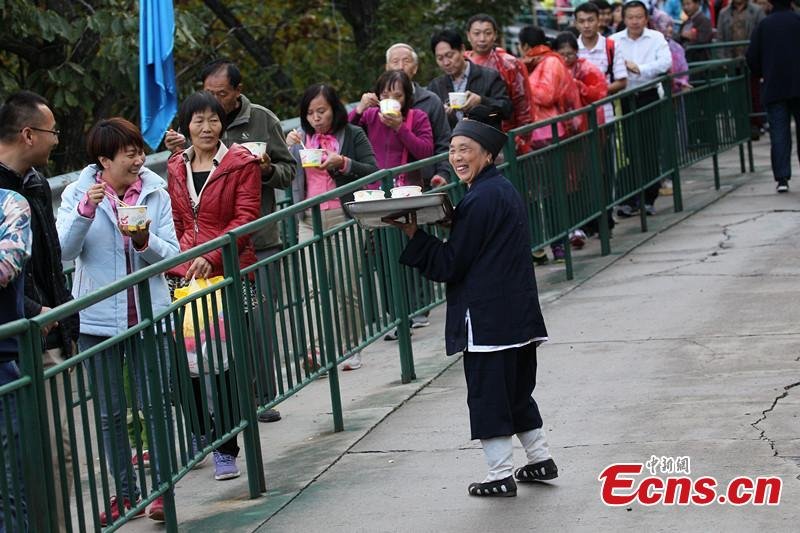 Taoists supply foods to tourists at view spot in Henan