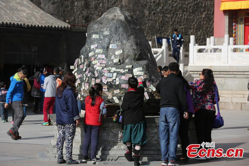 Tourists stick money on stone for good fortune