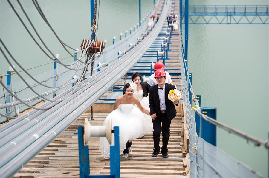 Young couples take wedding photos on suspension bridge in Chongqing