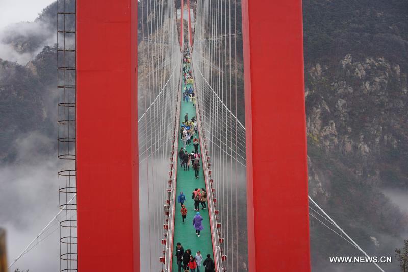 Tourists walk on pedestrian suspension bridge in E China