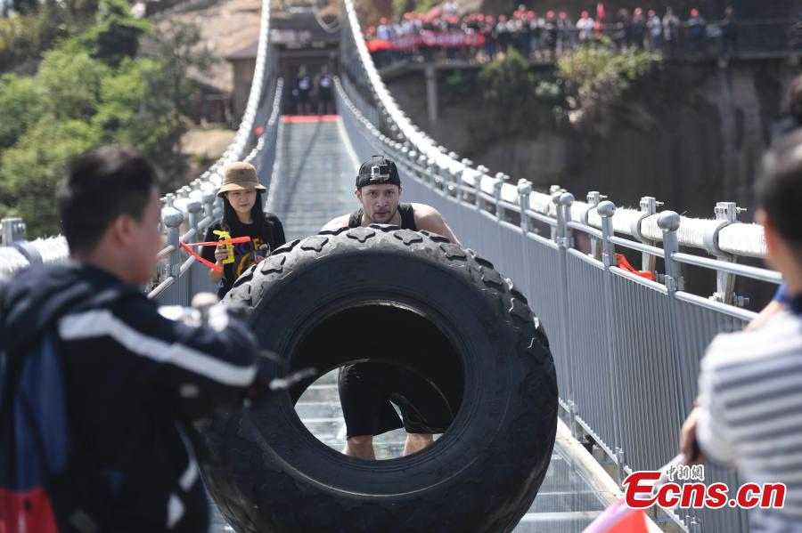 Tire flip challenges strongmen on suspended glass bridge