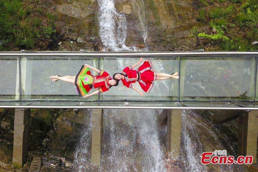 Glass walkway through waterfall opens in Hunan