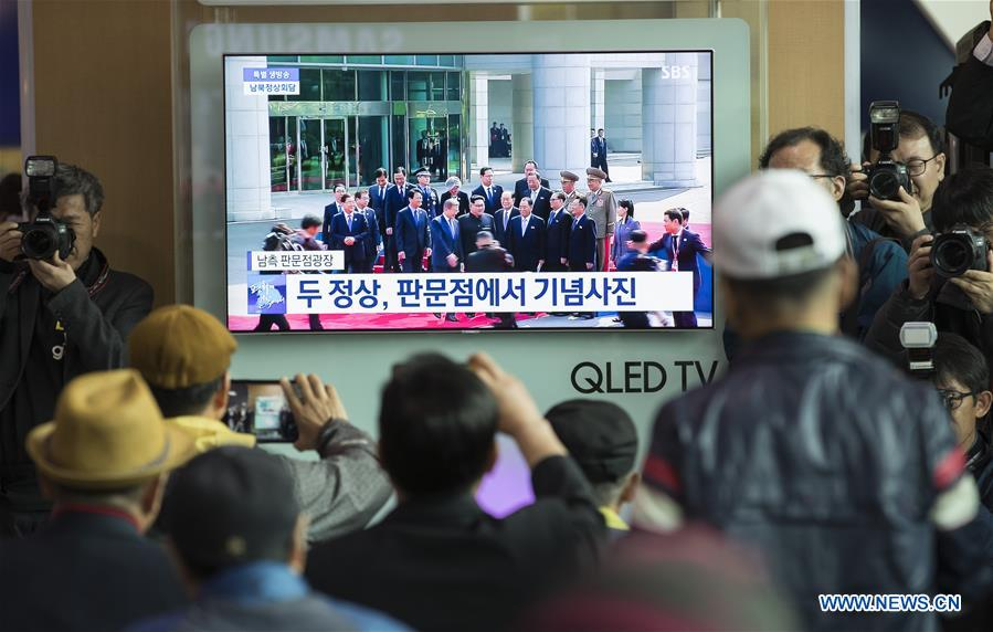 People watch news from screen on meeting of South Korean, DPRK leaders