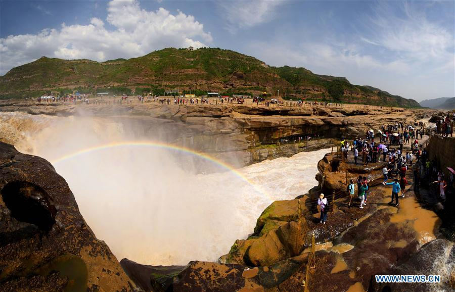 Tourists view Hukou Waterfall of Yellow River in NW China