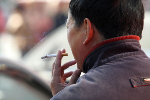 A man takes a cigarette break in a public place in Nantong, Jiangsu province, on Nov 30, 2013. (Provided to China Daily)