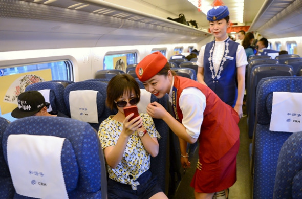 An attendant serves a passenger on a high-speed train at Hohhot East Train Station in the Inner Mongolia autonomous region on Thursday morning.