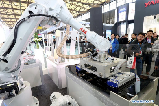 Visitors watch a robot during the Appliance & Electronics World Expo 2017 in east China's Shanghai, March 9, 2017. (Xinhua/Chen Fei)