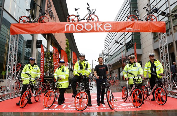 Manchester traffic police pose with Mobike bicycles at the launch of the bike-sharing services on June 29. Manchester marks the beginning of the Chinese company's global expansion, which popularizes the concept of sharing economy. XINHUA