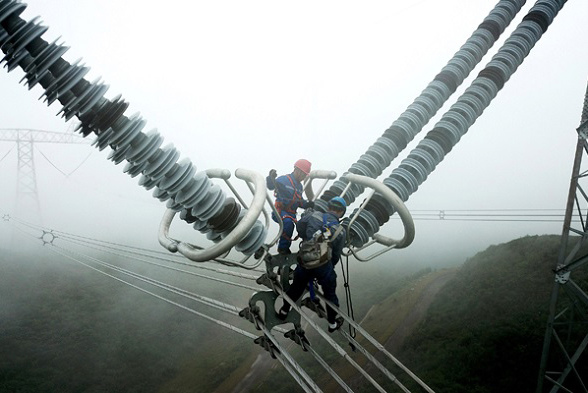 Two technicians from China Southern Power Grid inspect the Guizhou section of the ±800kV Northwestern Yunnan-Guangdong UHV DC power transmission project. (Photo/Xinhua)